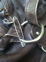 A safety pin locks a purse closed